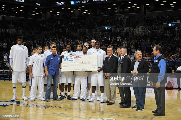 Kentucky Wildcat players and Papa John's Pizza founder John Schnatter pose for a picture and present a check from their recent Hurricane Sandy...