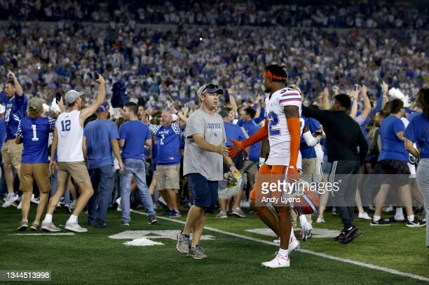 Kentucky Wildcats fan shakes hands with Mordecai McDaniel of the Florida Gators after the fans stormed the field to celebrate the 20-13 win over the...
