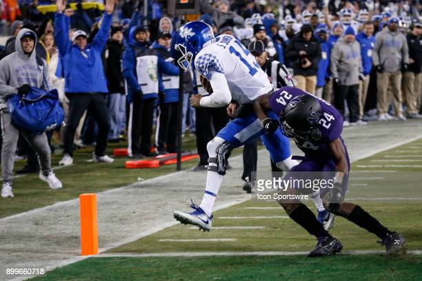 Kentucky Wildcats quarterback Stephen Johnson scores past Northwestern Wildcats corner back Montre Hartage during the Music City Bowl between the...
