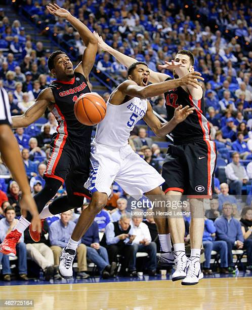 Kentucky's Andrew Harrison draws contact as he drives between Georgia's Kenny Gaines and Nemanja Djurisic at Rupp Arena in Lexington Ky on Tuesday...