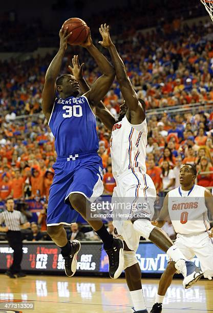 Kentucky's Julius Randle tries an offbalance shot as Florida's Patric Young defends in the first half at the Stephen C O'Connell Center in...