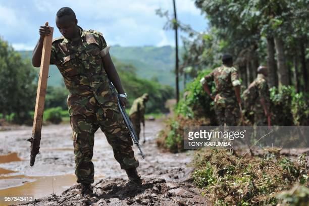 A Kenya Defence Force soldier patrols and inspects through mud and debris on May 11 2018 in search of bodies of victims after a dam burst its banks...