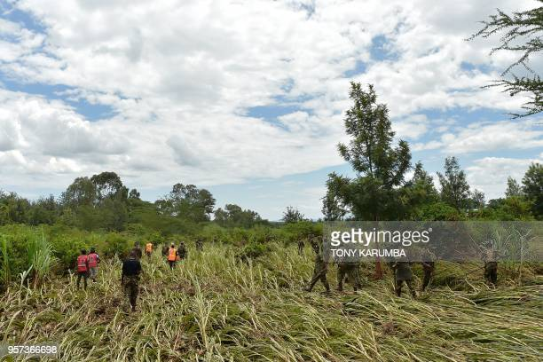 Kenya Defence Force soldiers patrol and inspect in a crop field on May 11 2018 in search of bodies of victims after a dam burst its banks sending...