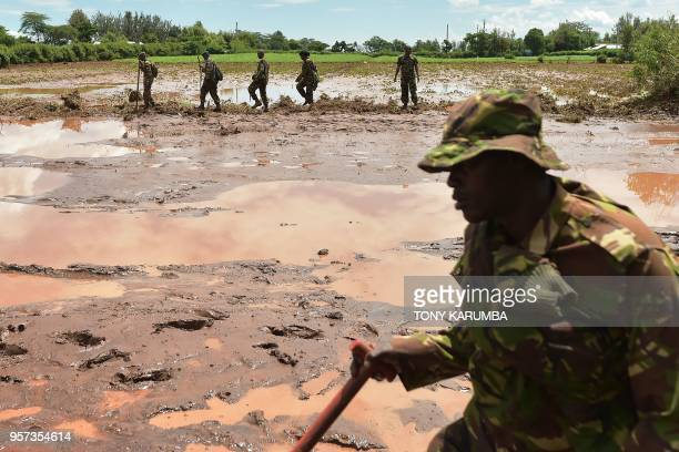 Kenya Defence Force soldiers patrol and inspect through mud and debris on May 11 2018 in search of bodies of victims after a dam burst its banks...