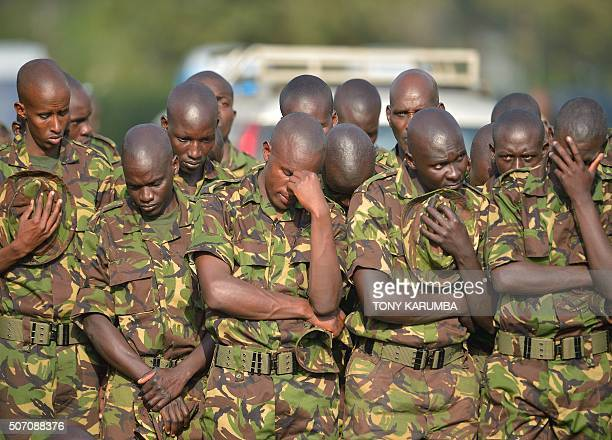 Kenya Defence Forces soldiers bow their heads during prayers for slain comrades at a memorial attended by Kenya's Uhuru Kenyatta Somalia's Hassan...