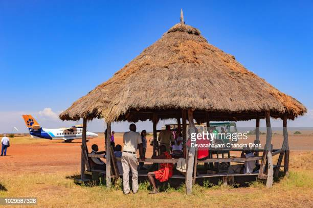 kenya, east africa - passenger facilities and boarding in progress at the olkiombo airstrip on the masai mara in the great rift valley - wildlife reserve stock photos and pictures