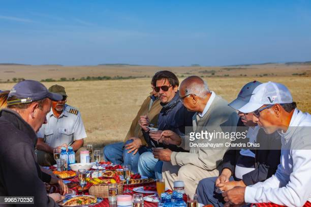 Kenya, East Africa - Tourists Enjoying A Champagne Breakfast On the Masai Mara National Reserve After An Early Morning Hot Air Balloon Safari