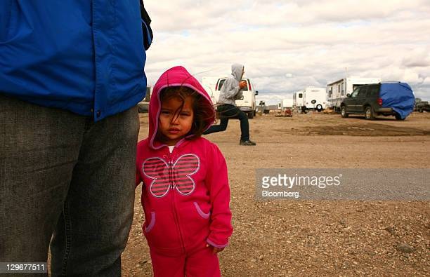 Kenya LeBaron stands next to her father while her brothers play on temporary worker housing grounds outside of Williston North Dakota US on Thursday...
