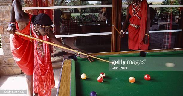 Kenya, Masai men playing billiards (blurred motion)