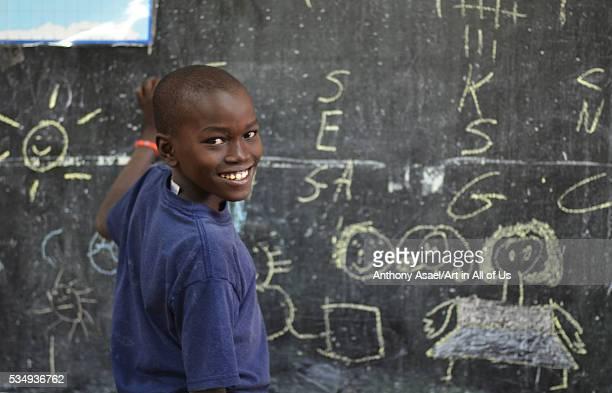 Kenya Nairobi little boy writing with chalk on blackboard