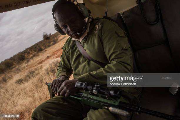 Kenya Wildlife Service veterinarian Dr Jeremiah Poghon prepares a dart gun which is used to sedate elephants during an elephant collaring operation...