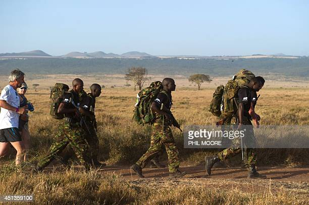 Kenyan army soldiers compete in full battle gear during the Safaricom marathon and halfmarathon held in the Lewa conservancy in Kenya's Laikipia...