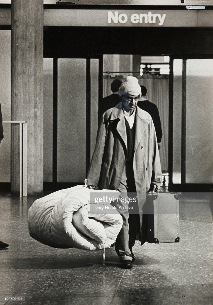 A Kenyan Asian migrant walks through customs at Heathrow, 1968. : News Photo