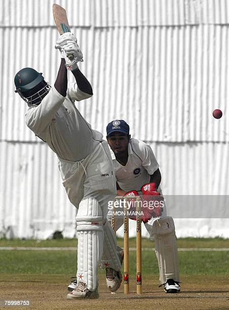 Kenyan batsman Peter Ongondo hits a delievery from India's bowler Irfan Pathan as India's wicket keeper Parthiv Patel awaits a catch 07 August 2007...