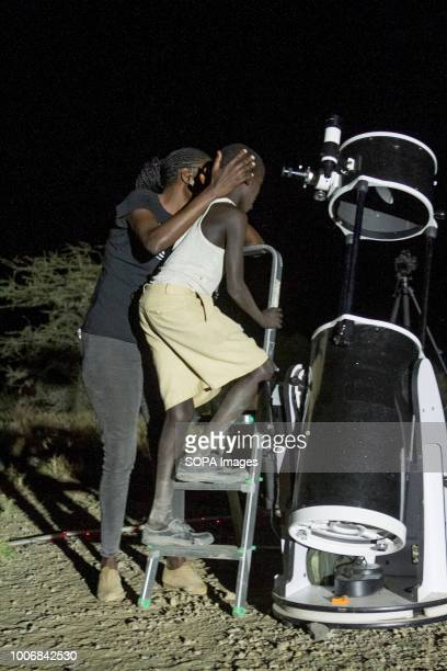 Kenyan Boy is seen being helped to look through a telescope People witness the Lunar Eclipse in Oloika Town Magadi Kenya The Moon completely covered...