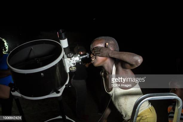 Kenyan Boy seen looking through a telescope People witness the Lunar Eclipse in Oloika Town Magadi Kenya The Moon completely covered the Earth's...