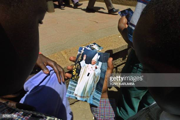Kenyan Catholics buy pictures of late Pope John paul II 03 April 2005 outside the Holy Family Basillica in Nairobi Kenya Kenyan President Mwai Kibaki...