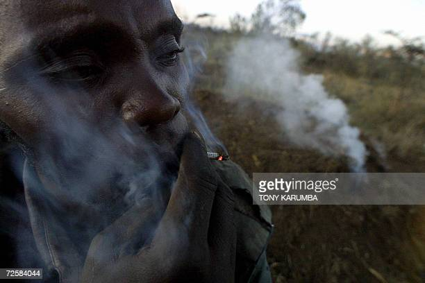Kenyan charcoal maker smokes as he tends to an earth mound under which wood is piled before baking it into charcoal 16 November 2006 in the Kenyan...