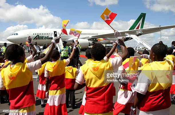 Kenyan children wave as the plane carrying the Pope prepares to depart on November 27 2015 in Nairobi on its way to Kampala Uganda