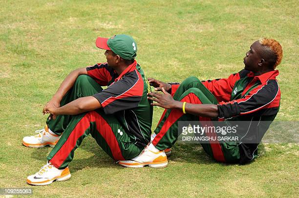 Kenyan cricketer Alex Obanda and teammate Rakep Patel stretch during a training session at The MA Chidambaram Stadium in Chennai on February 18 2011...