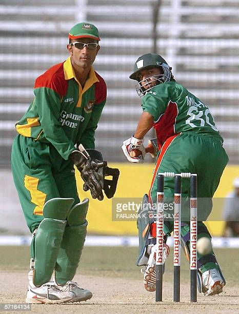 Kenyan cricketer Tanmay Mishra and Bangladeshi wicketkeeper Khaled Mashud watch a ball going towards the boundary during the third one day...