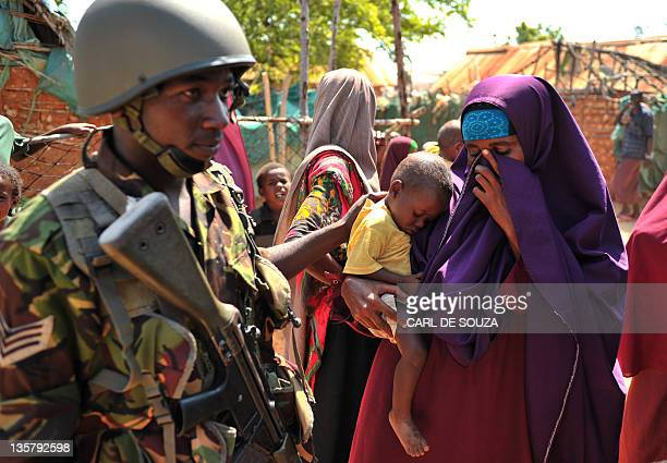 A Kenyan Defence Force soldier comforts a Somali woman with her sick child in Burgabo village Southern Somalia on December 14 2011 Burgabo is a...