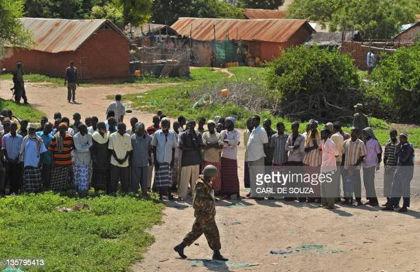 A Kenyan Defence Force soldier walks past villagers to an aid distribution point in Burgabo Southern Somalia on December 14 2011 Burgabo is a...