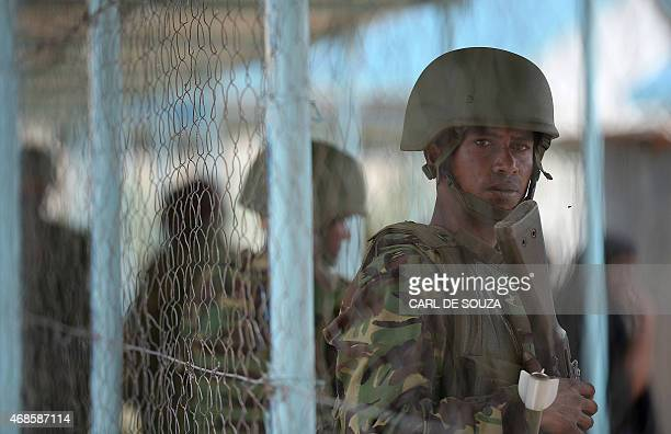 A Kenyan Defence forces soldier stands guard as people gather to view the bodies of the suspected attackers on the Garissa university at the mortuary...