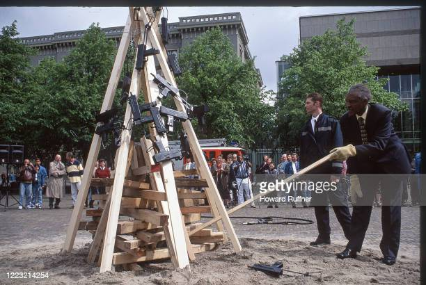 Kenyan diplomat Ambassador Bethuel Kiplagat lights 'Flame of Peace,' a bonfire of automatic weapons prior to the start of the Hague Appeal for Peace...