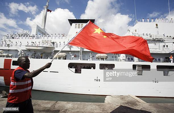 A Kenyan dock worker runs with a chinese flag during a good bye ceremony for the Chinese Naval hospital ship the Peace Ark before the vessel leaves...