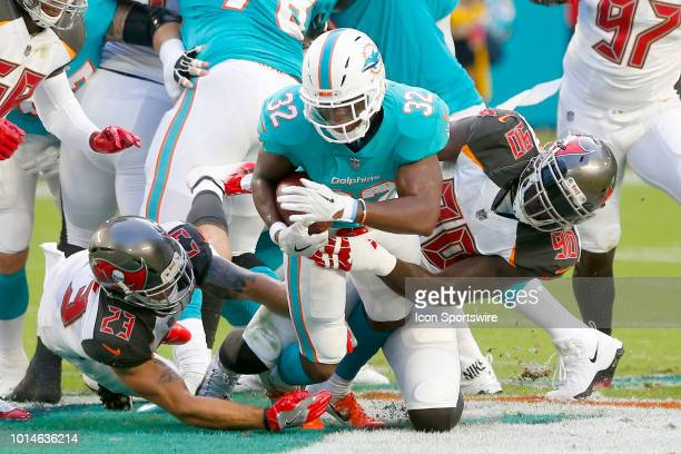 Kenyan Drake of the Dolphins is brought down by Chris Conte and Jason PierrePaul of the Buccaneeers during the preseason game between the Tampa Bay...