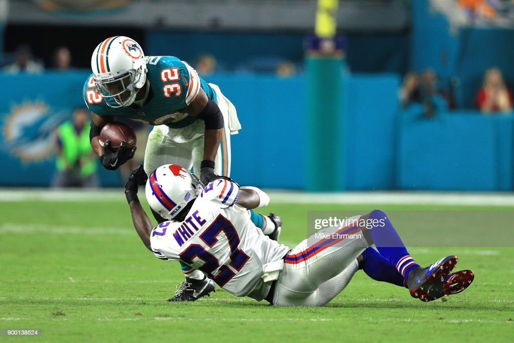 Kenyan Drake #32 of the Miami Dolphins breaks the tackles by Tre'Davious White #27 of the Buffalo Bills during the fourth quarter against the Buffalo Bills at Hard Rock Stadium on December 31, 2017 in Miami Gardens, Florida.