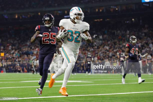 Kenyan Drake of the Miami Dolphins catches a pass and scores a touchdown defended by Kareem Jackson of the Houston Texans in the third quarter at NRG...