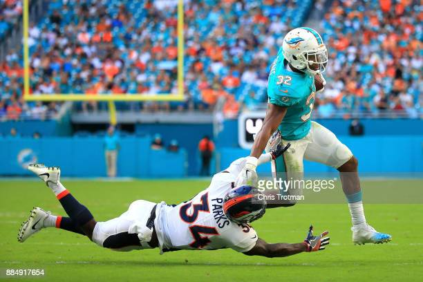 Kenyan Drake of the Miami Dolphins rushes during the third quarter against Will Parks of the Denver Broncos at the Hard Rock Stadium on December 3...
