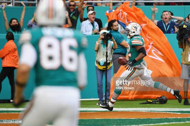 Kenyan Drake of the Miami Dolphins scores the game winning touchdown against the New England Patriots at Hard Rock Stadium on December 9 2018 in...