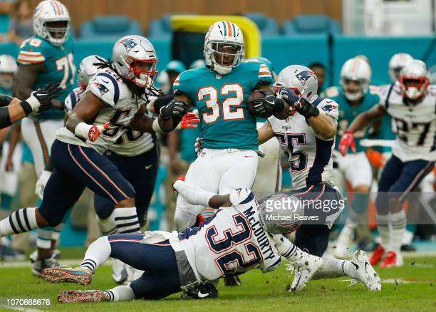 Kenyan Drake of the Miami Dolphins tries to avoid the tackle of Devin McCourty of the New England Patriots in the second half at Hard Rock Stadium on...