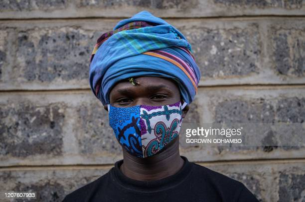 Kenyan fashion designer of Lookslikeavido David Avido poses for a portrait at his studio in Kibera Nairobi on March 18 with a mask he made that he...
