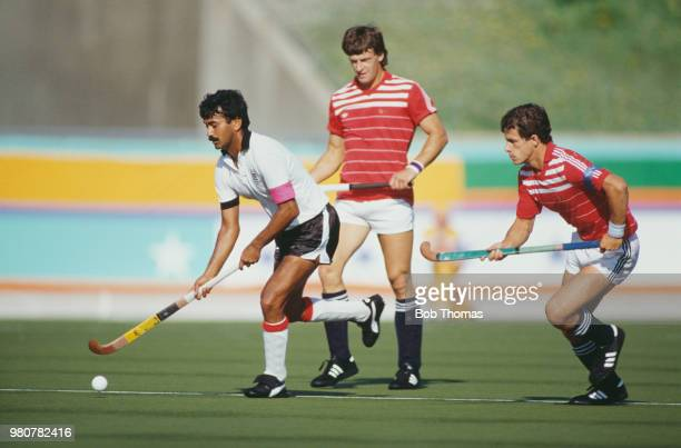 Kenyan field hockey player Brajinder Daved makes a run with the ball as Sean Kerly of Great Britain looks on during the pool B game between Great...