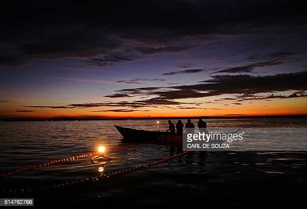 Kenyan fisherman pull up their nets in the early morning as they fish on Lake Victoria on March 3 2016 Nile perch which are common in the lake can...