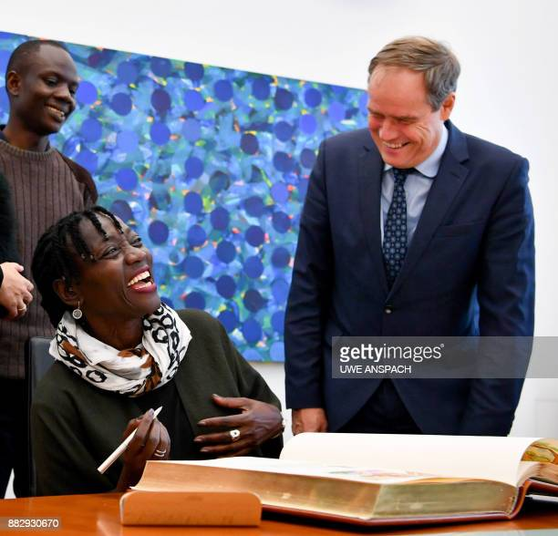 Kenyan Germanist author sociologist and halfsister of former US president Auma Obama smiles as she signs the Golden Book next to Heidelberg's mayor...