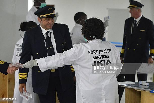 Kenyan health officials process arriving passengers at an observation area at the Jomo Kenyatta International Airport in the Kenyan capital Nairobi...