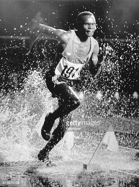 Kenyan Henry Nomo runs through water after completing a hurdle in the 3000 meter steeple chase at the 1976 Olympics in Montreal