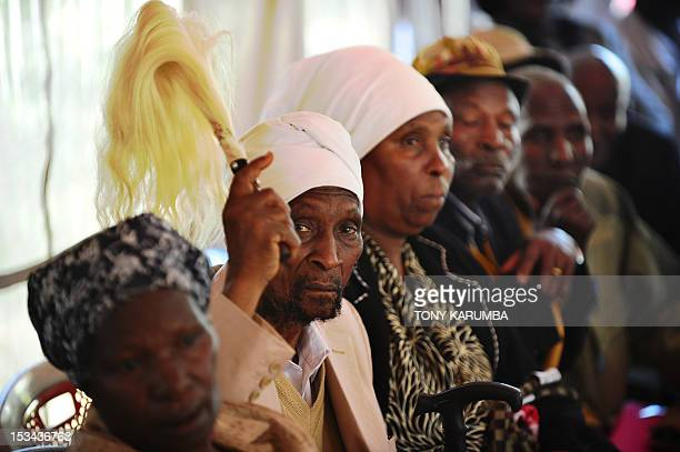 Kenyan independence struggle rebellion movement a MauMau veteran raises a traditional whisk as a gesture of victory in Nairobi on October 05 2012...