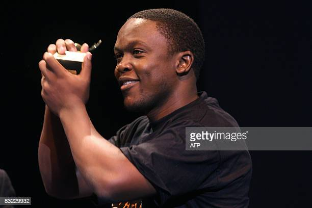 """Kenyan journalist Julius Mwelu jubilates after winning the """"Young reporter"""" prize in Bayeux, western France, on Octobrer 11, 2008 for a reporting in..."""