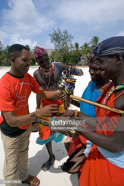 Kenyan man bargains with young Maasai tribesmen for bead handicrafts Diani Beach Kenya.