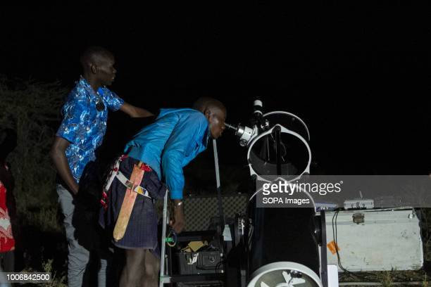 Kenyan man is seen being helped to look through a telescope People witness the Lunar Eclipse in Oloika Town Magadi Kenya The Moon completely covered...