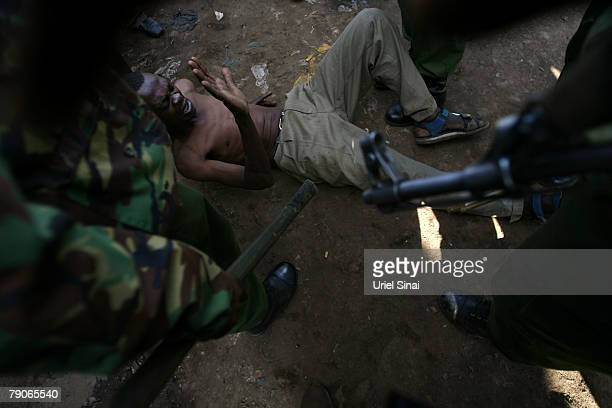 A Kenyan man lays on the ground surrounded by riot police during the second day of attempts to disperse renewed protests by supporters of Kenya's...