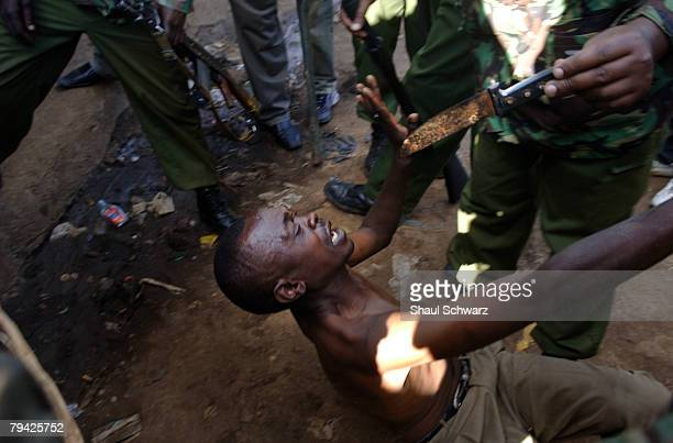 Kenyan man lays on the ground surrounded by riot police during the second day of attempts to disperse renewed protests by supporters of Kenya's...