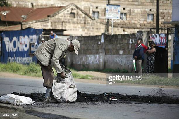 A Kenyan man recycles steel cords from burned tyres used as barricades after protestors in the Mathare neighborhood in Nairobi 29 December 2007...