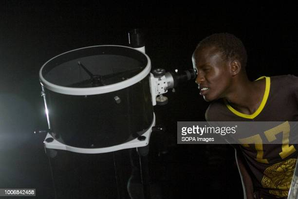 Kenyan man seen looking through a telescope People witness the Lunar Eclipse in Oloika Town Magadi Kenya The Moon completely covered the Earth's...
